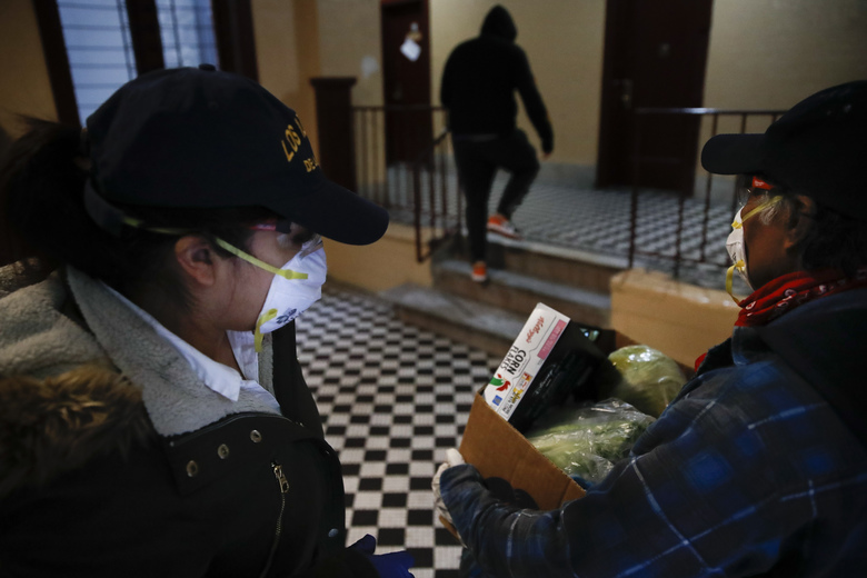 Sandra Perez, left, and Francisco Ramírez, right, enter a building to deliver a box of grocery donations to a family in need, Saturday, April 18, 2020, in the Bronx borough of New York. Some are former construction workers or cleaning ladies who lost their jobs and can barely pay rent, but they go out each day to deliver donated diapers, formula or food to families in need. Through Spanish-speaking chats in Facebook or word of mouth, small groups of immigrants find out who needs the help and they deliver it traveling by car or by foot, exposing themselves to the coronavirus that has already hit hard working-class neighborhoods. (AP Photo/John Minchillo)