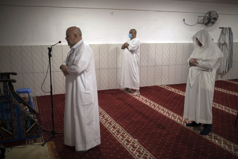 Abderrahmane Ghoul, imam of the Tahara Mosque broadcasts via radio the Friday prayer to confined worshippers at home during the coronavirus pandemic at a closed door service, in Marseille, southern France, Friday, April 24, 2020, during the first day of Ramadan. Millions of Muslims have started the holiest month on the Islamic calendar under the coronavirus lockdown or strict social restrictions. (AP Photo/Daniel Cole)