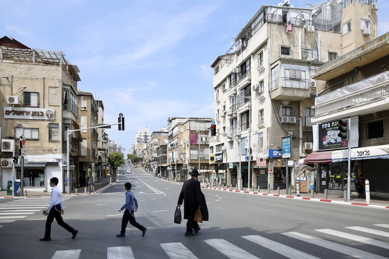 An Ultra orthodox man crosses a street in the city of Bnei Brak, a Tel Aviv suburb, Israel, Thursday, April 2, 2020. On Wednesday, Netanyahu ordered a police cordon around the largely ultra-Orthodox city of Bnei Brak, east of Tel Aviv, to limit movement to and from the city. Bnei Brak has the second highest number of coronavirus cases in Israel. (AP Photo/Ariel Schalit)