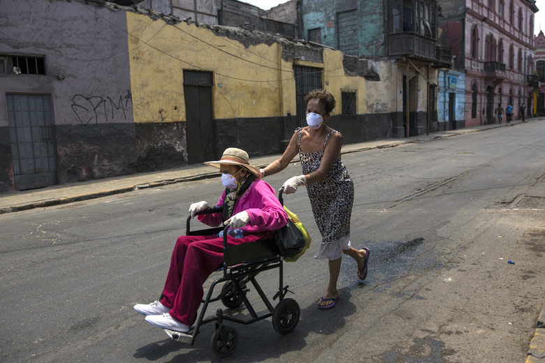 "In this March 18, 2020 photo, Flor Vaso pushes her 84-year-old mother Carmen Reyes in a wheelchair to their home, in Lima, Peru. Vaso and her mother reside with 44 other families in a large, deteriorated house near the presidential palace that has earned it the nickname ""Luriganchito,"" or ""Little Lurigancho,"" after San Pedro de Lurigancho, the country's most populous prison. (AP Photo/Rodrigo Abd)"