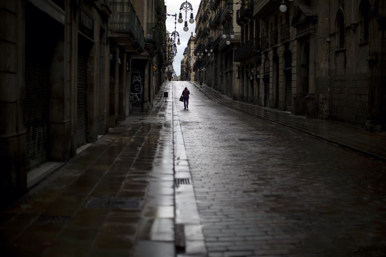 A man walks along an empty street in downtown Barcelona, Spain, Monday, April 20, 2020 as the lockdown to combat the spread of coronavirus continues. (AP Photo/Emilio Morenatti)