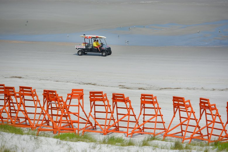 In this March 23, 2020 photo, ocean rescuers drive along Jacksonville Beach in Jacksonville, Fla. Mayor Lenny Curry says Duval County beaches are reopening Friday, April 17, 2020, with restricted hours, and they can be used only for walking, biking, hiking, fishing, running, swimming and surfing. (Bob Self/The Florida Times-Union via AP)