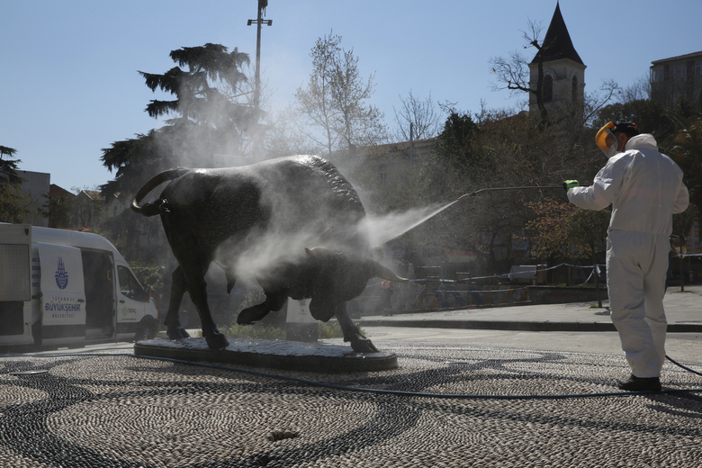 In this handout photo provided by Istanbul Mayor's office, workers clean and disinfect one of the city's iconic landmarks, the Bull, in Kadikoy Square amid the coronavirus outbreak, in Istanbul, Sunday, April 12, 2020. The new coronavirus causes mild or moderate symptoms for most people, but for some, especially older adults and people with existing health problems, it can cause more severe illness or death.(Istanbul Mayor's Office via AP)