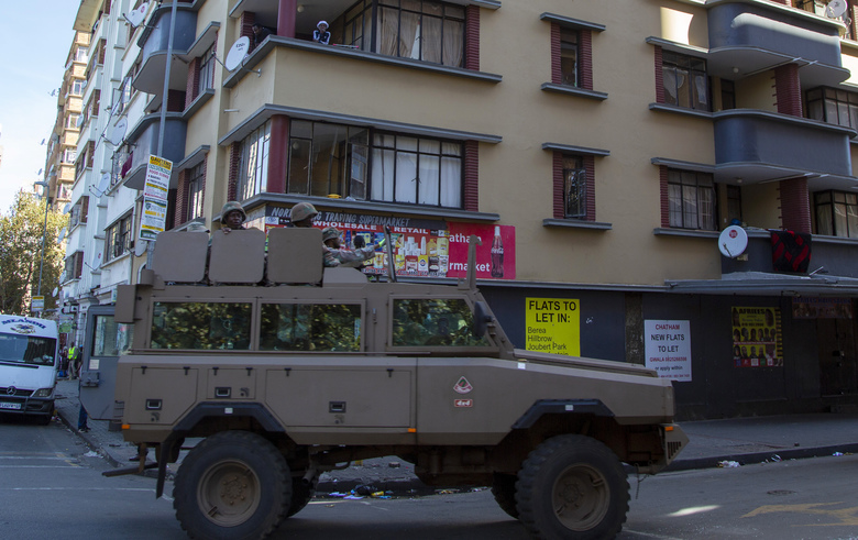 Residents stand on a balcony as a South African National Defence Forces vehicle patrol the street, in Johannesburg, South Africa, Tuesday, April 7, 2020. South Africa and more than half of Africa's 54 countries have imposed lockdowns, curfews, travel bans or other restrictions to try to contain the spread of COVID-19. The new coronavirus causes mild or moderate symptoms for most people, but for some, especially older adults and people with existing health problems, it can cause more severe illness or death. (AP Photo/Themba Hadebe)