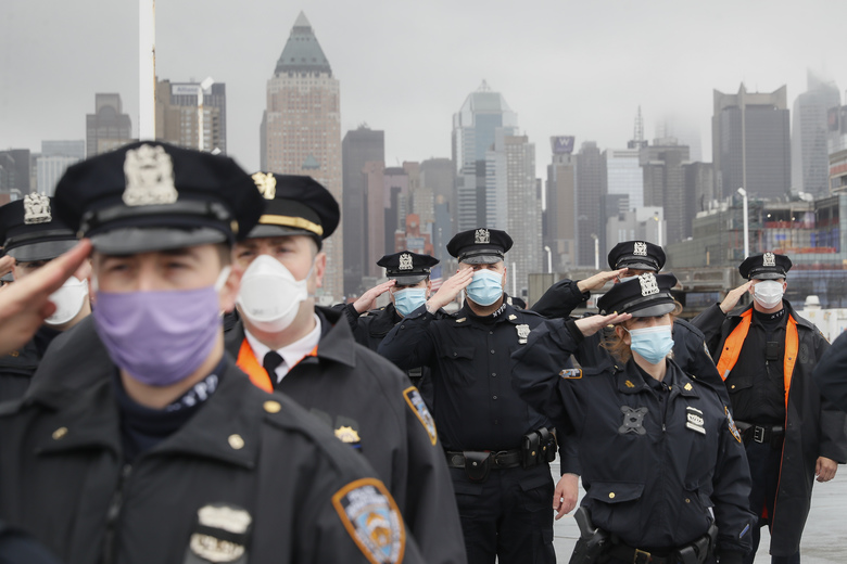 NYPD officers wearing masks to protect against cornavirus, salute the USNS Naval Hospital Ship Comfort as it is pushed out into the Hudson River by tugboats, Thursday, April 30, 2020, in the Manhattan borough of New York. (AP Photo/John Minchillo)