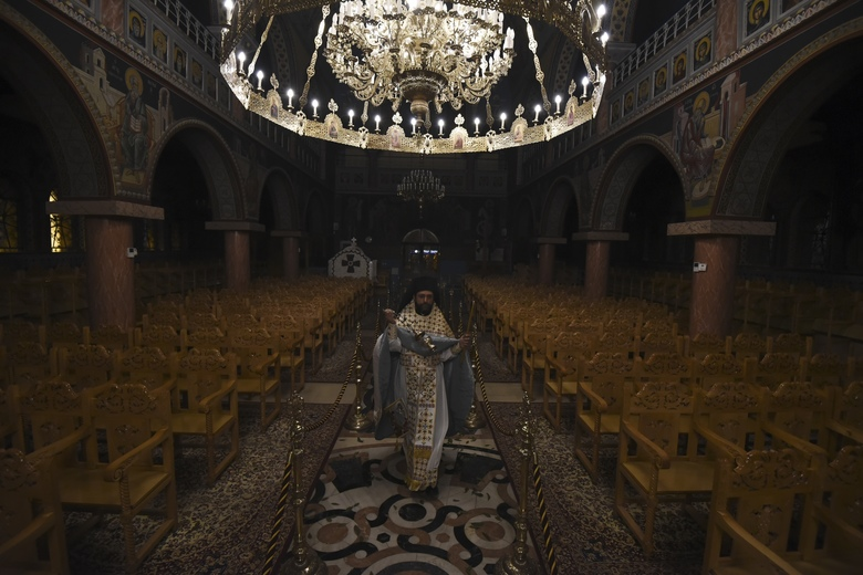 """A Greek Orthodox priest takes part in the Good Saturday ceremony, held without worshippers inside an empty church in the northern city of Thessaloniki, Greece, during a lockdown order by the government to prevent the spread of the coronavirus, on Sunday, April 19, 2020. Greeks celebrated the Resurrection of Christ very differently Saturday night: confined at home, instead of massively congregating in churches. And they had to do without the """"Holly Light"""" from Jerusalem, which arrived in Athens but was not distributed, as authorities remained ready to crack down on anyone who violated the strict curfew imposed almost a month ago. (AP Photo/Giannis Papanikos)"""