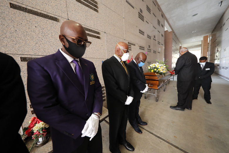 Pallbearers, who were among only 10 allowed mourners, stand by the casket for internment at the funeral for Larry Hammond, who died from the coronavirus, at Mount Olivet Cemetery in New Orleans, Wednesday, April 22, 2020. (AP Photo/Gerald Herbert)