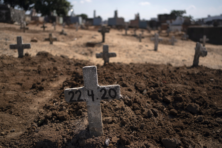 A cross with the date 22-4-20 marks the burial site of Edenir Rezende Bessa, who is suspected to have died of COVID-19, in Rio de Janeiro, Brazil, Wednesday, April 22, 2020. After visiting 3 primary care health units she wasaccepted ina hospital that treats new coronavirus cases, where she died on Tuesday.  (AP Photo/Leo Correa)