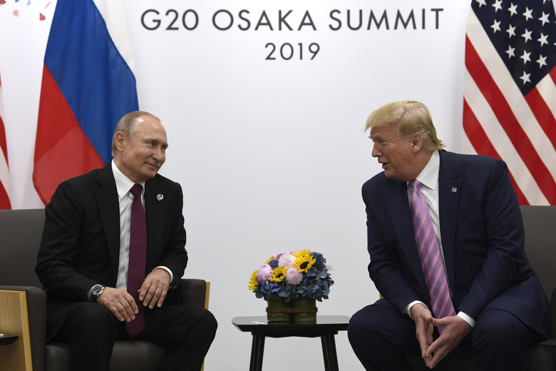 FILE – In this June 28, 2019, file photo, President Donald Trump, right, meets with Russian President Vladimir Putin during a bilateral meeting on the sidelines of the G-20 summit in Osaka, Japan. An odd new front in the U.S.-Russian rivalry has emerged as a Russian military cargo plane bearing a load of urgently needed medical supplies landed in New York's JFK airport. (AP Photo/Susan Walsh, File)