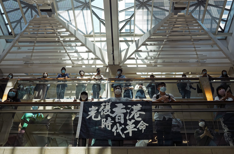 """Protestors wearing face masks raise a banner reading """" Liberate Hong Kong, Revolution of our time """" during a protest at a shopping mall in Hong Kong, Wednesday, April 29, 2020. Demonstrators gathered in a luxury mall chanting pro-democracy slogans, the latest in a string of protests over the past week. (AP Photo/Vincent Yu)"""