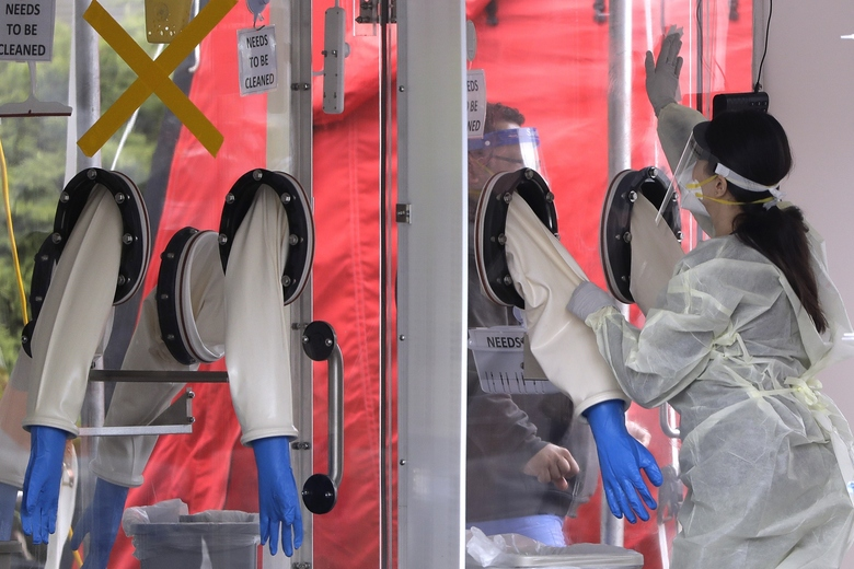 A medical worker cleans protective gloves at a coronavirus testing tent outside MGH Healthcare Center, Monday, April 20, 2020, in Chelsea, Mass. (AP Photo/Steven Senne)