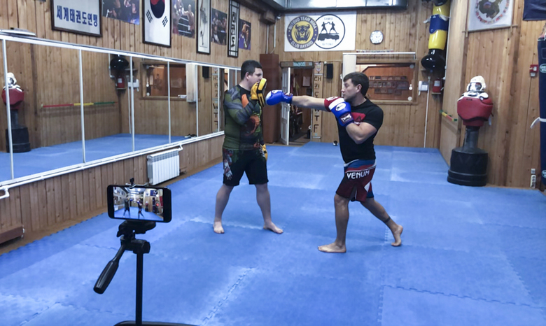 In this photo taken via online video call on Thursday, April 16, 2020, Mixed martial arts trainer Roman Martinov films a video lesson for his trainees following the closure of all city gyms, sports schools and training sections in Moscow, Russia. Russians from many walks of life are struggling to adapt to working remotely because of the coronavirus outbreak. The shutdown has driven many businesses to the verge of collapse and made millions jobless, according to estimates.(AP Photo/Pavel Golovkin)