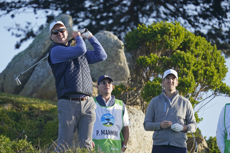 FILE – In this Feb. 7, 2020, file photo, Peyton Manning, left, follows his shot from the 11th tee of the Monterey Peninsula Country Club Shore Course as his brother Eli Manning, right, stands nearby during the second round of the AT&T Pebble Beach National Pro-Am golf tournament in Pebble Beach, Calif. Peyton Manning plans to play a round of golf with an All In Challenge winner two guests, and then go to a restaurant for dinner with the winner and 10 guests. His recently retired brother, Eli, offered the Corvette he received as the MVP of the New York Giants' Super Bowl win over the Patriots in February 2012. (AP Photo/Tony Avelar, File)