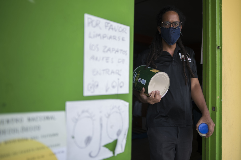 The coordinator of Comedores Sociales (Social Canteens), Giovanni Roberto, a non-profit entity dedicated to offering hot meals in the middle of the Covid-19 pandemic, carries supplies before handing out an order in Caguas, Puerto Rico, Wednesday, April 29, 2020. Puerto Rico's government is refusing to open school cafeterias amid a coronavirus pandemic as a growing number of unemployed parents struggle to feed their children. (AP Photo/Carlos Giusti)