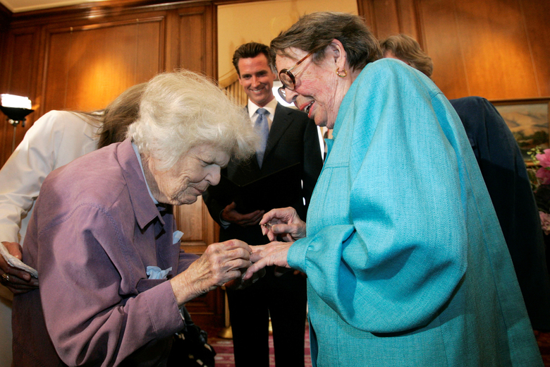 FILE – In this June 16, 2008, file photo, Del Martin, left, places a ring on her partner Phyllis Lyon, right, during their wedding ceremony officiated by then-San Francisco Mayor Gavin Newsom, center, at City Hall in San Francisco. Pioneering gay rights activist Lyon, who was among the first same-sex couples to marry in California when it became legal to do so, has died at her San Francisco home. Lyon died at age 95 of natural causes Thursday, April 9, 2020. (AP Photo/Marcio Jose Sanchez, File)
