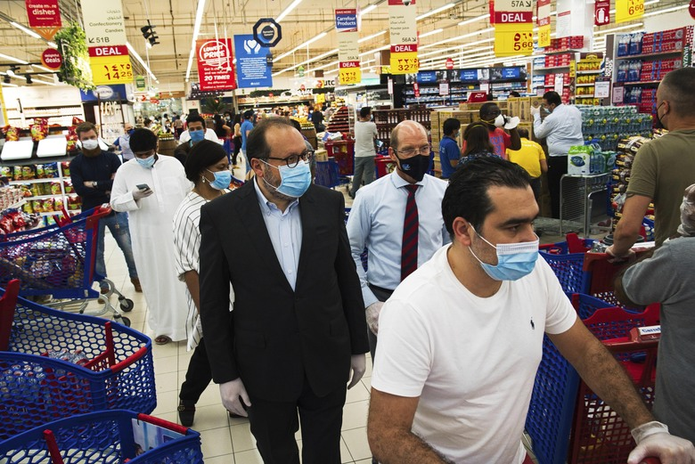 In this Sunday, April 19, 2020 photo, Majid Al Futtaim CEO Alain Bejjani, center left, and store manager Arnaud Bouf, center, walk through heavy shopping traffic during the coronavirus pandemic in the world's busiest Carrefour supermarket, at the Mall of the Emirates in Dubai, United Arab Emirates. One of the biggest private employers in the Middle East hasn't yet cut salaries or laid off any of its 44,000 workers, but the pandemic is changing how Majid Al Futtaim, the company that owns and operates hundreds of grocery stores and more than two dozen malls, thinks about food security, retail and tourism. (AP Photo/Jon Gambrell)
