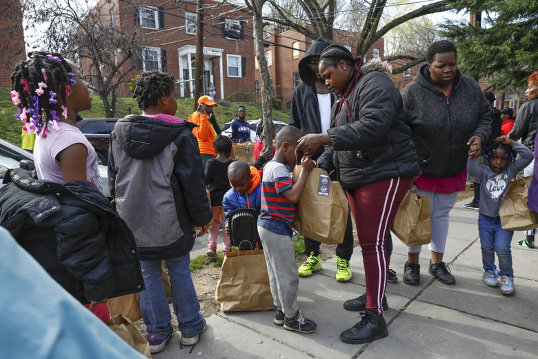 In this March 29, 2020, photo, Kahlil Middleton, 5, center, looks inside a bag containing a hot meal held by his mother, Alexis Whitley, near their apartment in southeast Washington. Whitley worked at Nationals Stadium but was laid off as a result of the coronavirus closures. Neighborhood deliveries are part of a new Martha's Table initiative, along with community partners, to get needed food directly to the neighborhoods that they serve.  (AP Photo/Jacquelyn Martin)