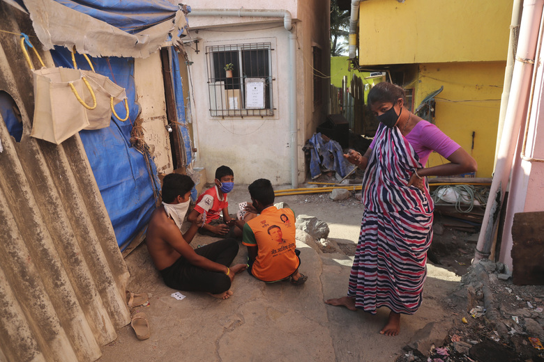 In this April 1, 2020, photo, Mina Ramesh Jakhawadiya, right, scolds her son Ritik Ramesh, wearing red t-shirt not to play outside in a slum in Mumbai, India. Jakhawadiya makes a living selling cheap plastic goods with her husband on the streets of Mumbai. For her, the order means 21 days in a 6-by-9 foot room with five people, no work, a couple days of food and very less cash. As governments around the world debate ways to slow the spread of coronavirus, India has launched one of the most draconian social experiments in human history, locking down its entire population, including  hundreds of millions of people who struggle to survive on a few dollars a day. (AP Photo/Rafiq Maqbool)
