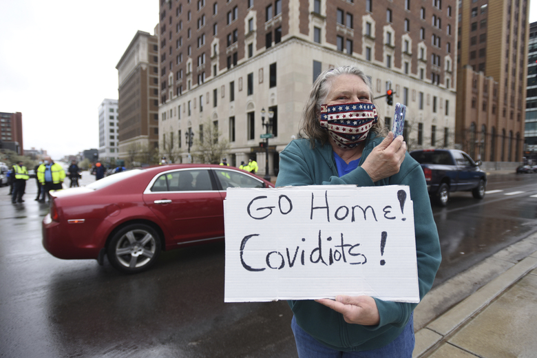 Karen Spitler of Lansing , an counter-protesters holds a sign during a rally at the state Capitol in Lansing, Mich., Thursday, April 30, 2020. Hoisting American flags and handmade signs, protesters returned to the state Capitol to denounce Gov. Gretchen Whitmer's stay-home order and business restrictions due to COVID-19, while lawmakers met to consider extending her emergency declaration hours before it expires. (Matthew Dae Smith/Lansing State Journal via AP)