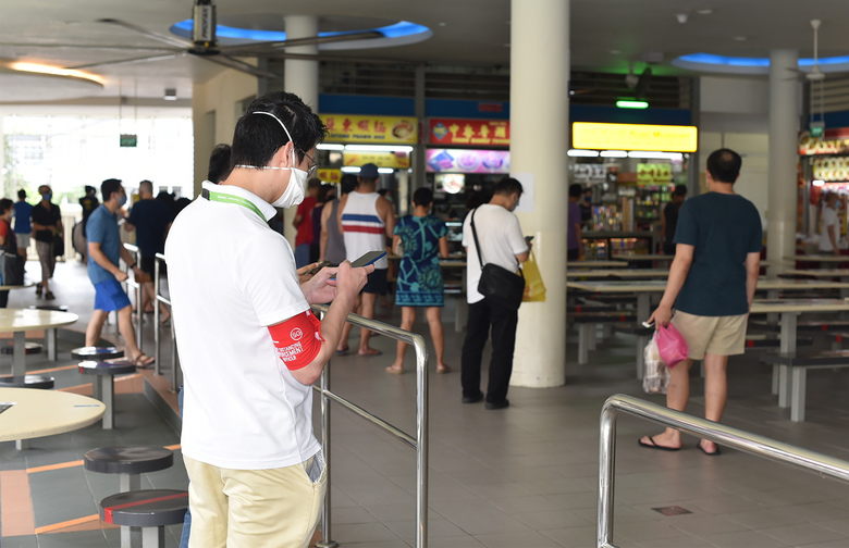 A safe-distancing enforcement officer wearing a red armband checks his phone at a food court in Singapore on Saturday, April 18, 2020. The officers have been deployed throughout the Southeast Asian city-state to ensure people maintain distance from one another as it grapples with a spike in coronavirus cases. (AP Photo/YK Chan)
