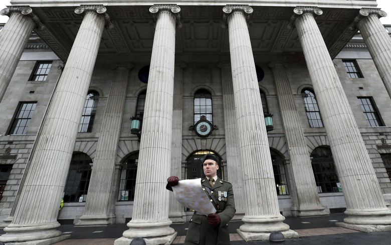 Captain Darren Reilly of the Irish Defence Forces, reads a copy of The Proclamation outside the GPO on Dublin's O'Connell Street during the annual 1916 Easter Commemoration, which because of the coronavirus was held in the courtyard inside the building, in Dublin, Ireland, Sunday April 12, 2020.  The 1916 Proclamation declared Ireland's independence from the United Kingdom.  The highly contagious COVID-19 coronavirus has impacted on nations around the globe, many imposing self isolation and exercising social distancing when people move from their homes. (Brian Lawless / PA via AP)