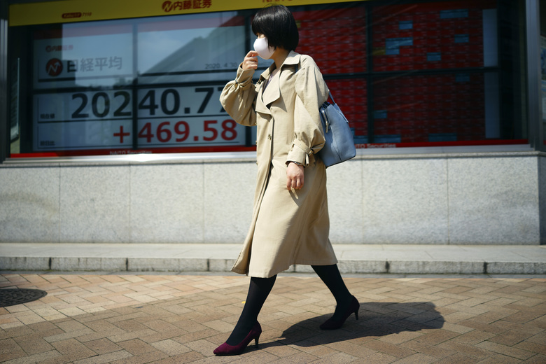 A woman walks past an electronic stock board showing Japan's Nikkei 225 index at a securities firm in Tokyo Thursday, April 30, 2020. Asian shares advanced on Thursday, riding a wave of optimism about a possible treatment for the coronavirus that set off a rally on Wall Street powerful enough to override data showing the U.S. economy had logged its worst quarterly performance since 2009. (AP Photo/Eugene Hoshiko)
