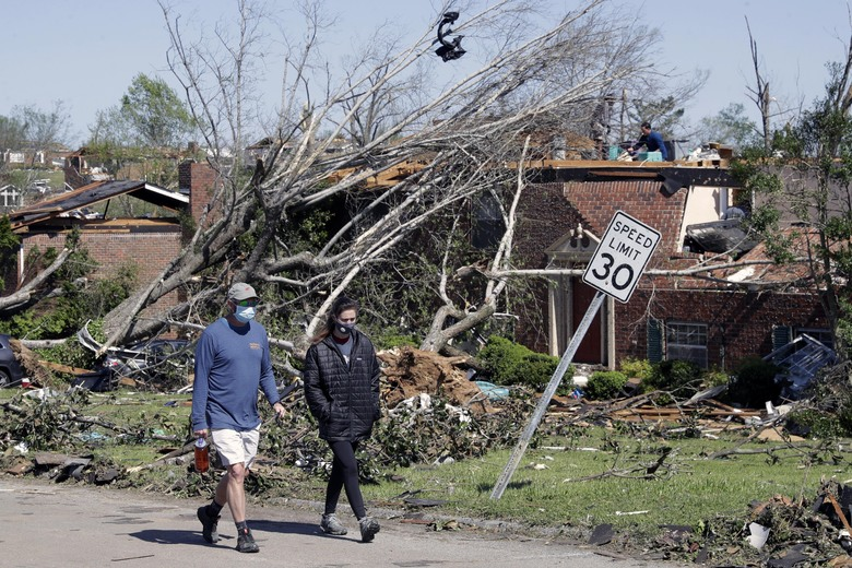 People walk up a street of damaged homes Tuesday, April 14, 2020, in Chattanooga, Tenn. Tornadoes went through the area Sunday, April 12. (AP Photo/Mark Humphrey)