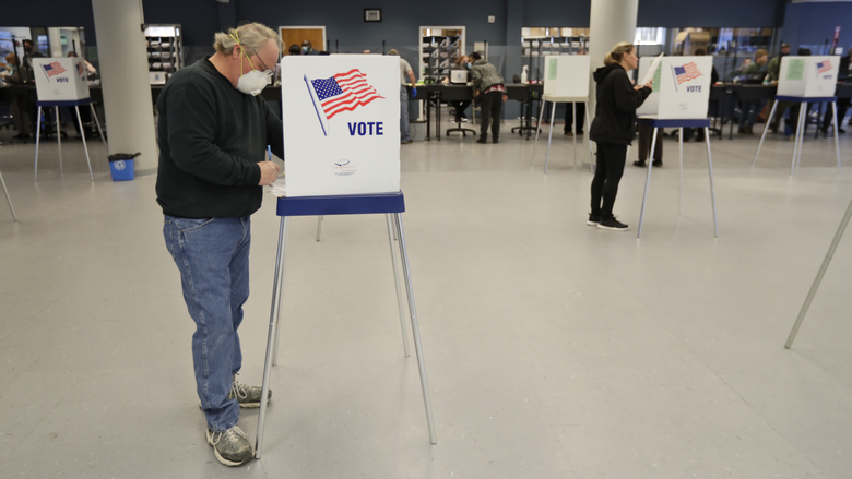 Jerome Fedor, left, votes using social distancing at the Cuyahoga County Board of Elections, Tuesday, April 28, 2020, in Cleveland, Ohio. The first major test of an almost completely vote-by-mail election during a pandemic is unfolding Tuesday in Ohio, offering lessons to other states about how to conduct one of the most basic acts of democracy amid a health crisis. (AP Photo/Tony Dejak)