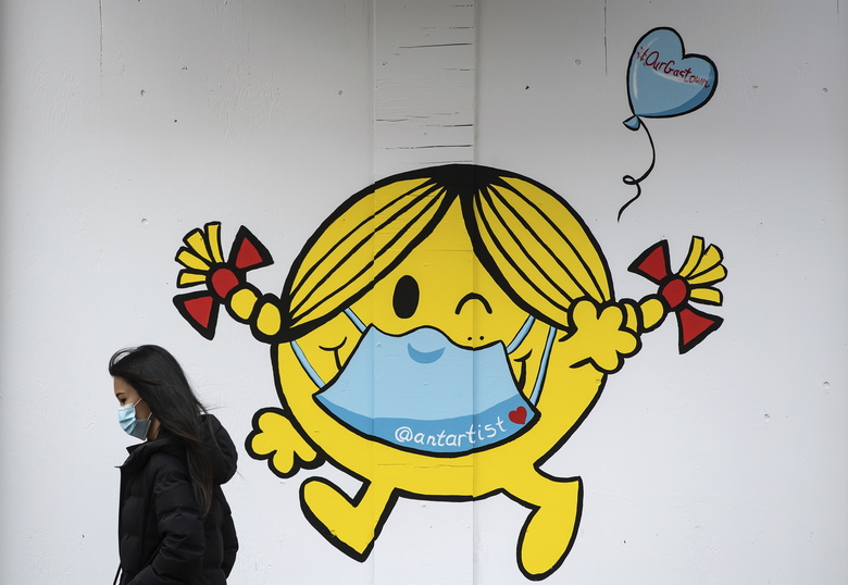 A woman wearing a face mask walks past artwork of author and illustrator Roger Hargreaves' 'Little Miss Sunshine' character wearing a face mask, painted on the outside of a boarded up business in downtown Vancouver, on Sunday, April 19, 2020. (Darryl Dyck/The Canadian Press via AP)