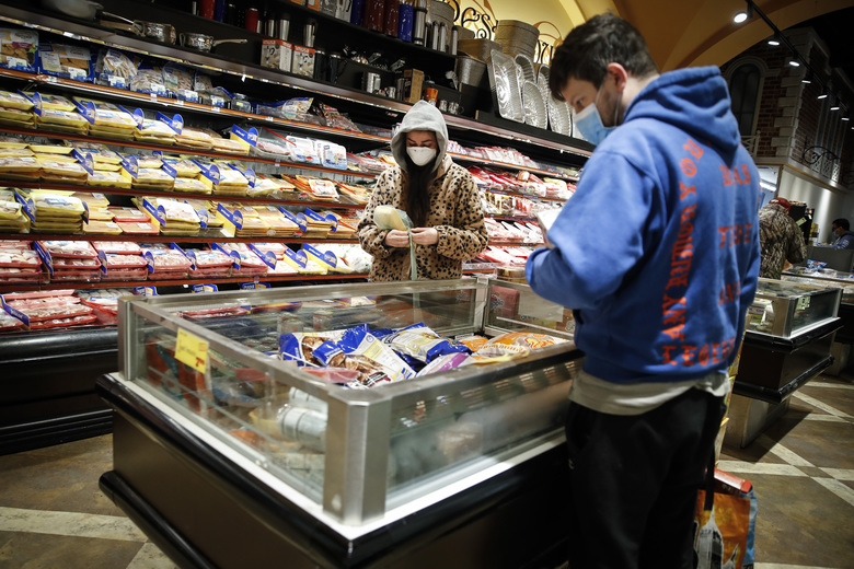 Shoppers wear personal protective equipment as they browse the meat section of a grocery store Saturday, April 18, 2020, in the Harlem neighborhood of the Manhattan borough of New York. (AP Photo/John Minchillo)