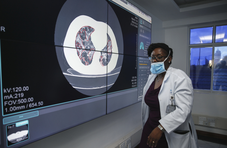 A doctor walks past a screen used for training showing an example CT scan of the lungs of a coronavirus patient, at Kenyatta National Hospital in Nairobi, Kenya Thursday, April 2, 2020. The new coronavirus causes mild or moderate symptoms for most people, but for some, especially older adults and people with existing health problems, it can cause more severe illness or death. (AP Photo/Brian Inganga)