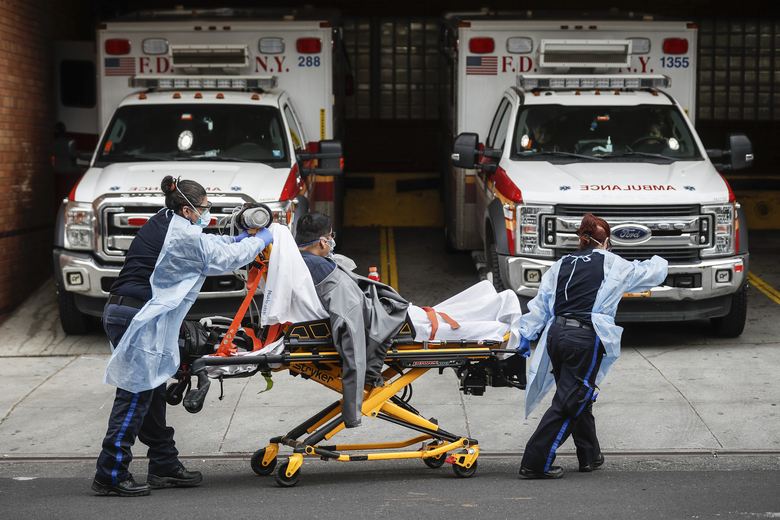 FILE – In this April 7, 2020, file photo, patients are brought into Wyckoff Heights Medical Center by staff wearing personal protective gear due to COVID-19 concerns, in the Brooklyn borough of New York. The coronavirus has breathed fresh life into old conspiracy theories and inspired a mishmash of new ones, with a cast of villains that includes Bill Gates, 5G wireless technology, the United Nations and President Donald Trump's political foes. The baseless claims spreading on social media also feature videos taken outside hospitals treating COVID-19 patients. (AP Photo/John Minchillo, File)
