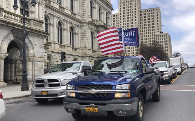 In this image made from video, a flag bearing truck is driven along Washington Avenue during a protest outside the State Capitol in Albany, N.Y., Wednesday, April 22, 2020. Several dozen protesters waved signs calling on New York Gov. Andrew Cuomo to lift social distancing restrictions as a cavalcade of horn-honking, flag-bedecked cars and pickup trucks slowly circled the block to snarl noontime traffic. (AP Photo/Mary Esch)