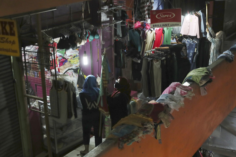 Clothes sellers prepare to open their shops at a quiet market in Jakarta, Indonesia, Friday, April 10, 2020. Authorities began stricter measures to halt the new coronavirus' spread in Indonesia's capital Friday, with its normally congested streets empty after death toll spiked in the past week. (AP Photo/Achmad Ibrahim)