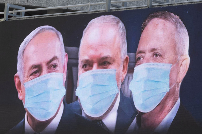 "Israeli Prime Minister Benjamin Netanyahu, left, Israeli Former Defense Minister and leader of the Yisrael Beiteinu (Israel Our Home) right-wing party Avigdor Lieberman, center, and Blue and White party leader Benny Gantz, are shown on a billboard wearing masks in the Israeli city of Ramat Gan, near Tel Aviv, Sunday, March 29, 2020. Gantz, Netanyahu's chief rival, was chosen on Thursday as the new speaker of parliament, an unexpected step that could pave the way to a power-sharing deal between the two men as the country grapples with a worsening coronavirus crisis. The billboard calling for unity reads: ""Benny, Avigdor and Bibi take off your masks, the people want unity."" (AP Photo/Sebastian Scheiner)"