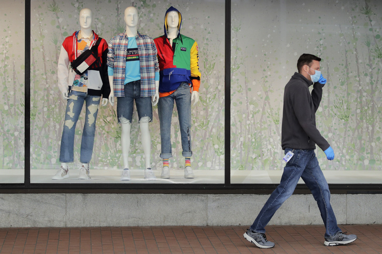 A man walks past mannequins in the windows of the Macy's store in the Downtown Crossing area of Boston, on Wednesday. U.S. retail sales plummeted in March, an unprecedented decline, as the viral outbreak forced an almost complete lockdown of commerce nationwide.  (Charles Krupa / The Associated Press)