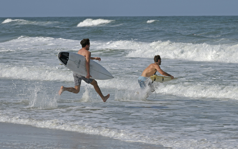 Surfers  run into the waves as the beaches opened on a limited  Friday, April 17, 2020 on Jacksonville Beach, Fla. Gov. Ron DeSantis  has given the green light for some beaches and parks to reopen if it can be done safely after being closed because of the coronavirus.  DeSantis' announcement on Friday came as north Florida beaches became among the first to allow beach-goers to return since the closures.  (Will Dickey/The Florida Times-Union via AP)