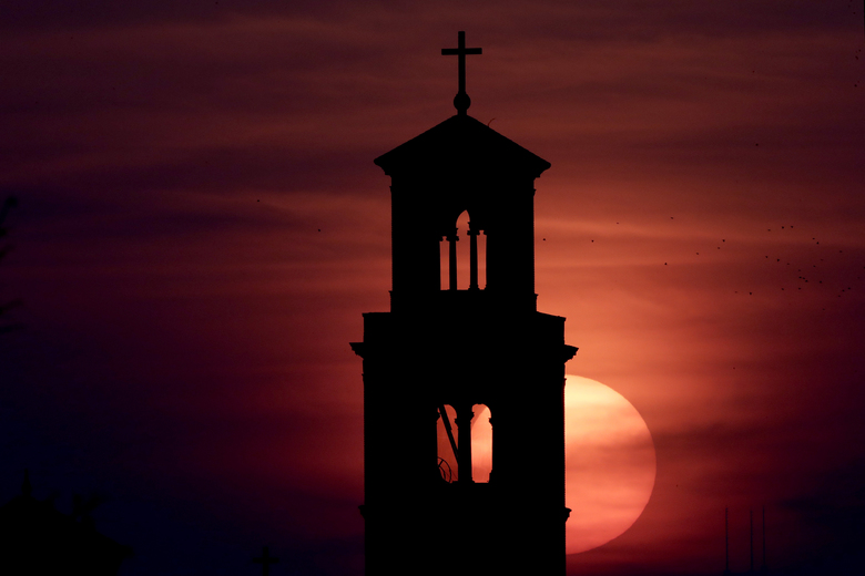Our Lady of Sorrows Catholic Church is silhouetted against the rising sun in Kansas City, Mo., Wednesday, April 8, 2020. With Easter Sunday in four days, many churches are looking for ways to celebrate the occasion in light of stay-at-home orders and restrictions on gathering in an effort to slow the spread of the new coronavirus. (AP Photo/Charlie Riedel)