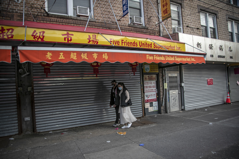 A couple walks in front of shuttered shops in the Chinatown in the Brooklyn borough of New York, on Tuesday, March 24, 2020. (AP Photo/Wong Maye-E)