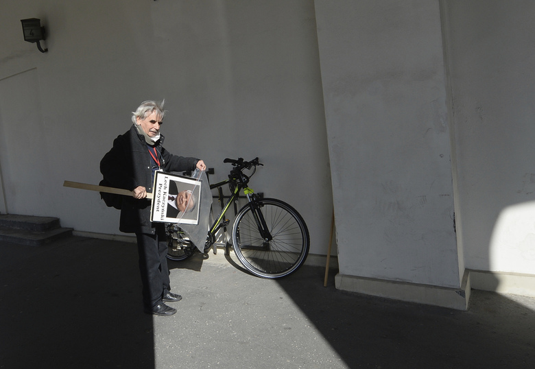 A man with a portrait of the late President Lech Kaczynski readies to go home after a scaled-down observance in memory of Kaczynski and 95 other prominent Poles who were killed in a plane crash in Russia 10 years ago, in Warsaw, Poland, on Friday, April 10, 2020. The observances were scaled down to just a few people and no crowd under social distancing regulations against the spread of the coronavirus. The new coronavirus causes mild or moderate symptoms for most people, but for some, especially older adults and people with existing health problems, it can cause more severe illness or death..(AP Photo/Czarek Sokolowski)