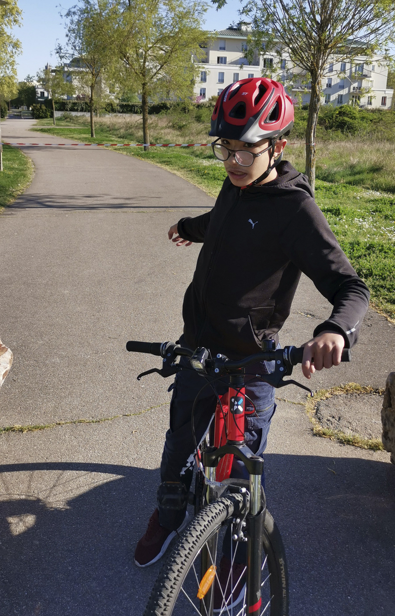 Mohammed, a 14-year-old with autism, on his bike outside his home Wednesday April 15, 2020 in Mantes-la-Jolie, west of Paris.  France's confinement measures provide an exception for people with autism that allows them to go out in places where they are accustomed to. Coronavirus lockdown is proving an ordeal for kids with disabilities and their families who are having to care for them at home because special schools have been shut down to curb infections. (Courtesy of family via AP)