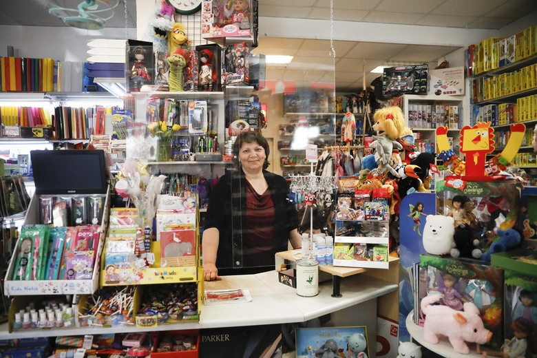 Galina Hooge owner of a small stationery and toy store poses for a photo behind plexiglass, to protect against the coronavirus, in her shop in Berlin, Germany, Wednesday, April 22, 2020. Galina Hooge opened her store for the first time in over a month, welcomed the loosening of restrictions, but remained wary.  (AP Photo/Markus Schreiber)