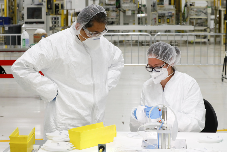 Sungchin Hong, left, and Christine Cugini work on validating N95 protective masks in Warren, Mich., Thursday, April 23, 2020. General Motors has about 400 workers at the now-closed transmission plant in suburban Detroit. All over the country, blue-collar and salaried workers have raised their hands to make medical equipment as companies repurpose factories to answer calls for help from beleaguered nurses, doctors and paramedics who are treating patients with the highly contagious new coronavirus COVID-19. (AP Photo/Paul Sancya)