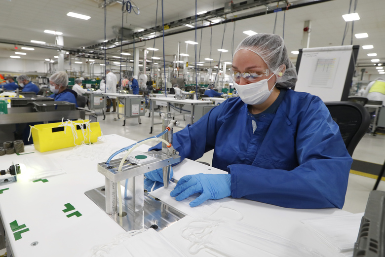 Amantha Combs works on making protective masks in Warren, Mich., Thursday, April 23, 2020. General Motors has about 400 workers at the now-closed transmission plant in suburban Detroit. All over the country, blue-collar and salaried workers have raised their hands to make medical equipment as companies repurpose factories to answer calls for help from beleaguered nurses, doctors and paramedics who are treating patients with the highly contagious new coronavirus COVID-19. (AP Photo/Paul Sancya)