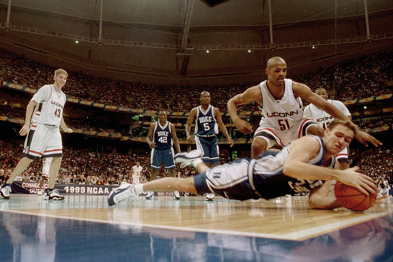 FILE – In this March 29, 1999, file photo, Duke's Chris Burgess tries to keep the ball from going out of bounds as Connecticut's Edmund Saunders (51) watches in the first half of the championship game of the NCAA college basketball Final Four, in St. Petersburg, Fla. UConn won 77-74. (AP Photo/Dave Martin, File)