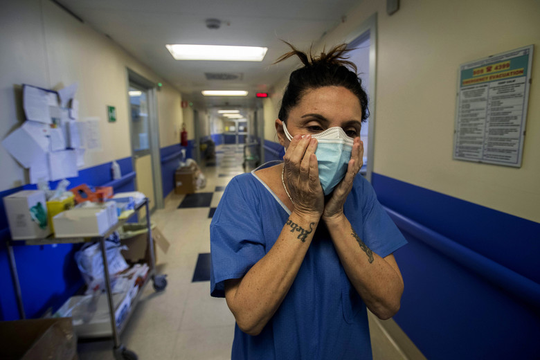 In this photo taken on Friday, April 10, 2020 nurse Cristina Settembrese fixes two masks to her face during her work shift in the COVID-19 ward at the San Paolo hospital in Milan, Italy. Settembrese spends her days caring for COVID-19 patients in a hospital ward, and when she goes home, her personal isolation begins by her own choice. (AP Photo/Luca Bruno)