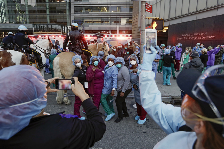 Medical workers pose for photographs as police officers and pedestrians cheer for them outside NYU Medical Center, April 16, 2020, in New York. (AP Photo/Frank Franklin II)