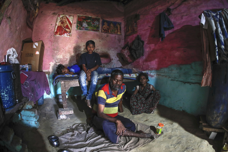 Rajesh Dhaikar sits idle with children in his small house, in Prayagraj, India, April 5, 2020. Dhaikar has a small balloon stall in a nearby market, selling plastic bursts of red and blue and yellow one at a time, and rarely earning more than $2.50 a day. His wife, Suneeta, makes about $20 a month cleaning homes. They have five children, ranging in age and a bank account with about $6.50 in it. (AP Photo/Rajesh Kumar Singh)