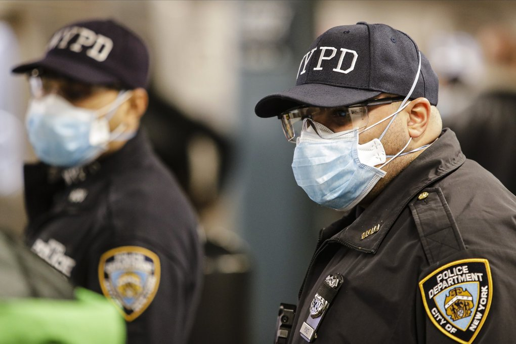New York police officers clear trains at the Coney Island – Stillwell Avenue Terminal on Tuesday. (Frank Franklin II / The Associated Press)
