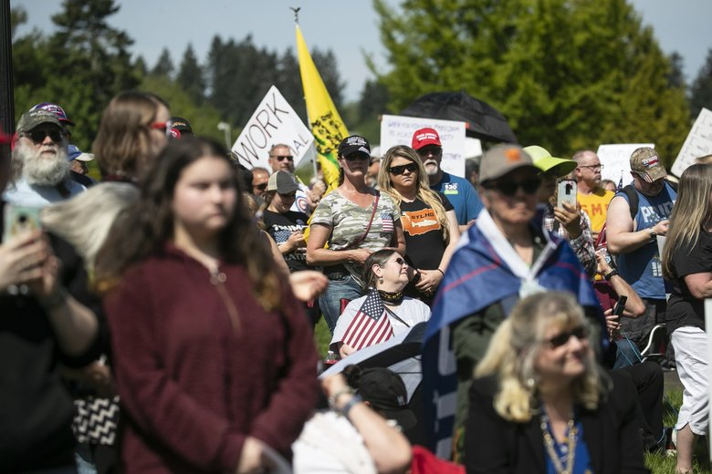 Demonstrators gather against coronavirus restrictions during a Liberty Alliance of Washington State rally Saturday at the Capitol in Olympia. (Amanda Snyder / The Seattle Times)